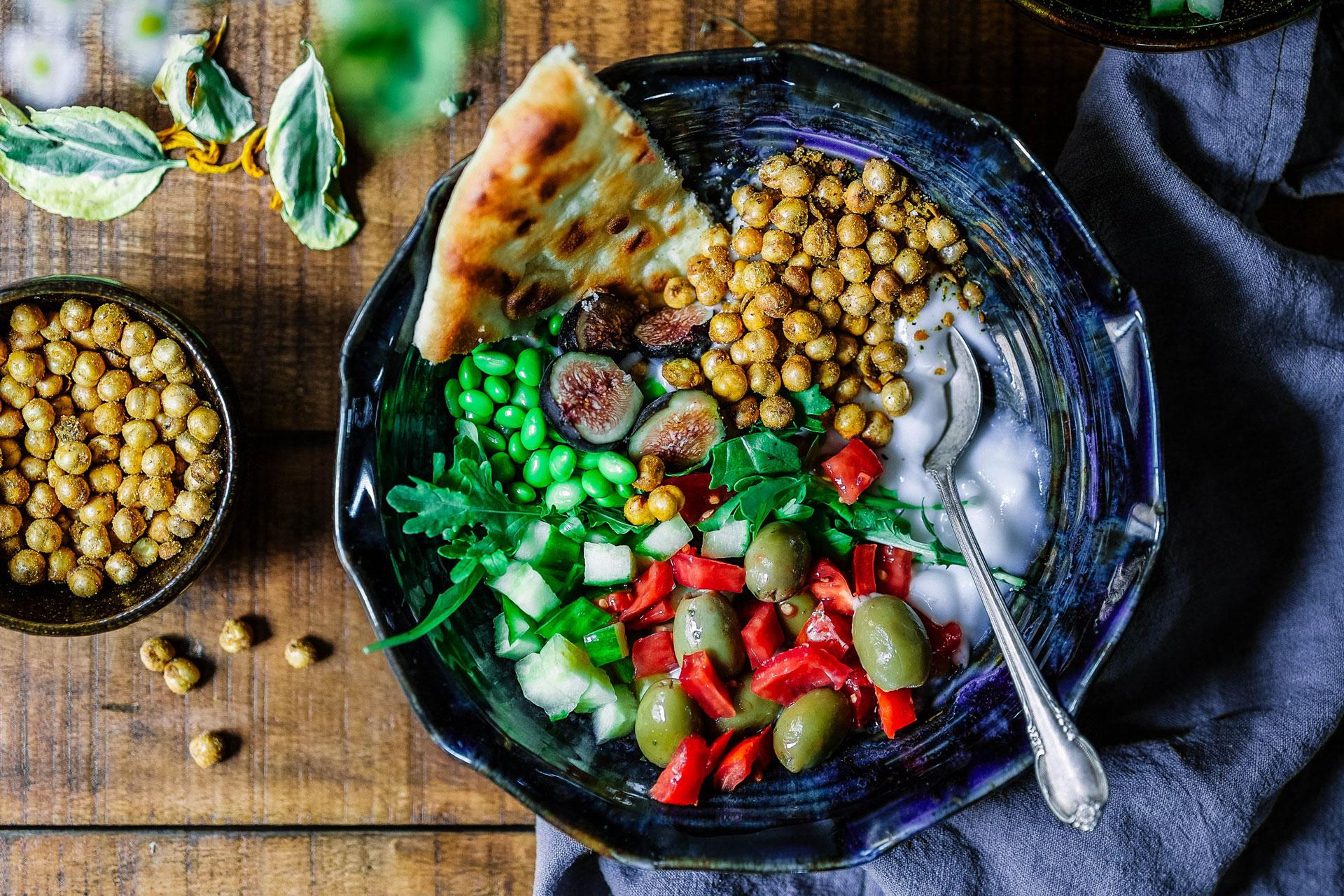 Beans, herbs, olives, yogurt in bowl
