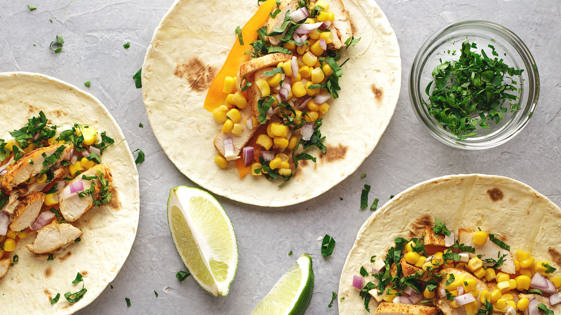 Latin American fast food tacos with chicken meat and vegetables on the gray stone background