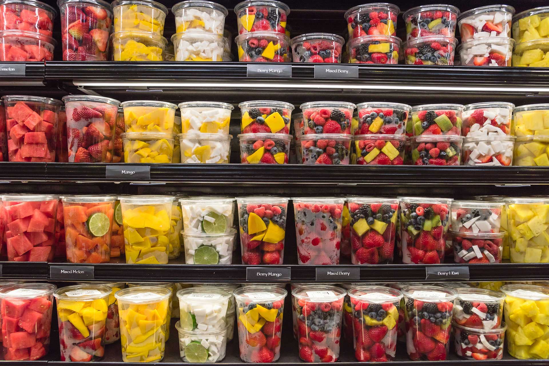 fresh fruit in plastic containers on grocery shelves