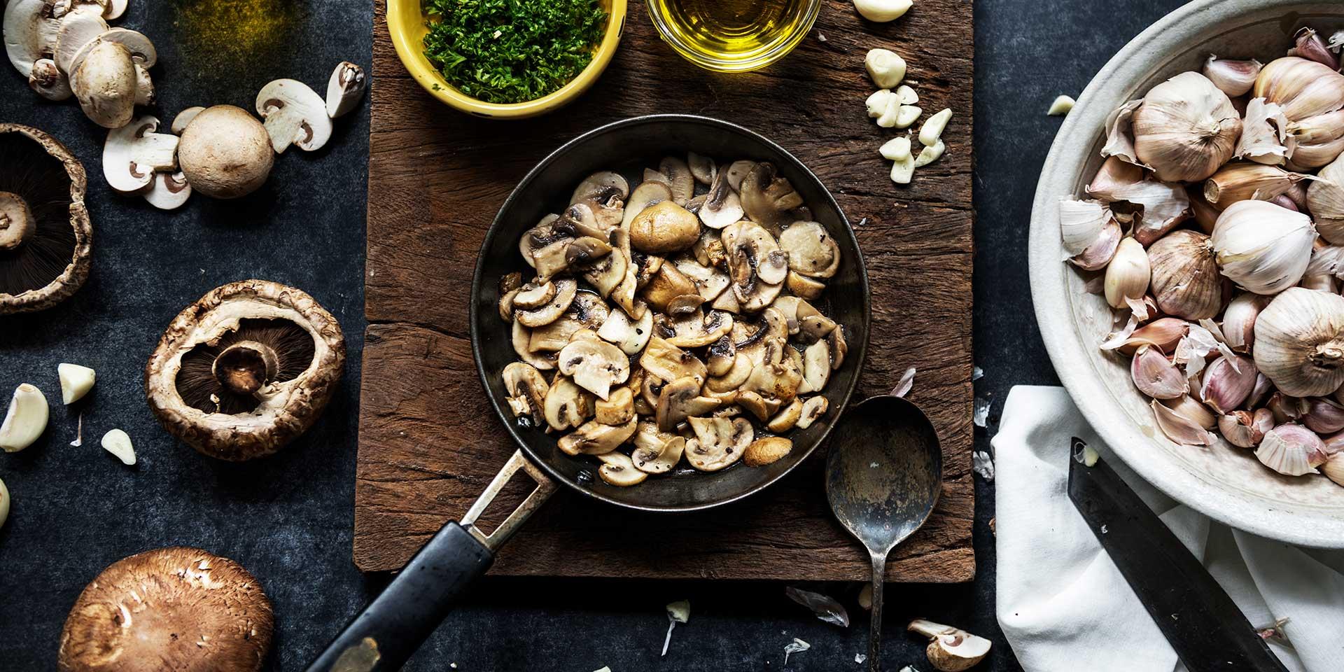 sliced mushroom pieces being cooked, garlic, herbs, portobello mushrooms